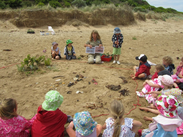 Torquay Montessori kindergarten students surround GORCC Conservation Officer Georgina Beale as she teaches them about the coast.