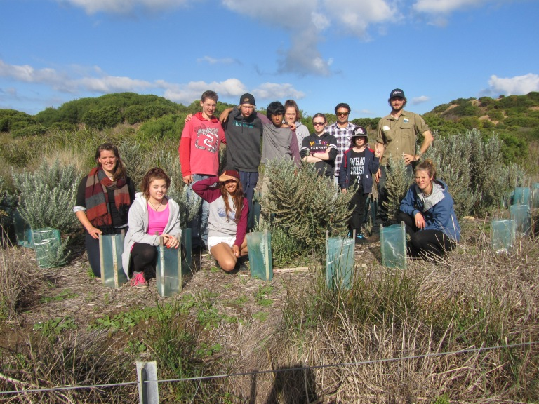 GORCC activity Education Leader Peter Crowcroft (back right) with Northern Bay College Teacher Shane Thompson (chequered shirt) and students with self-sustaining Olearia plant.