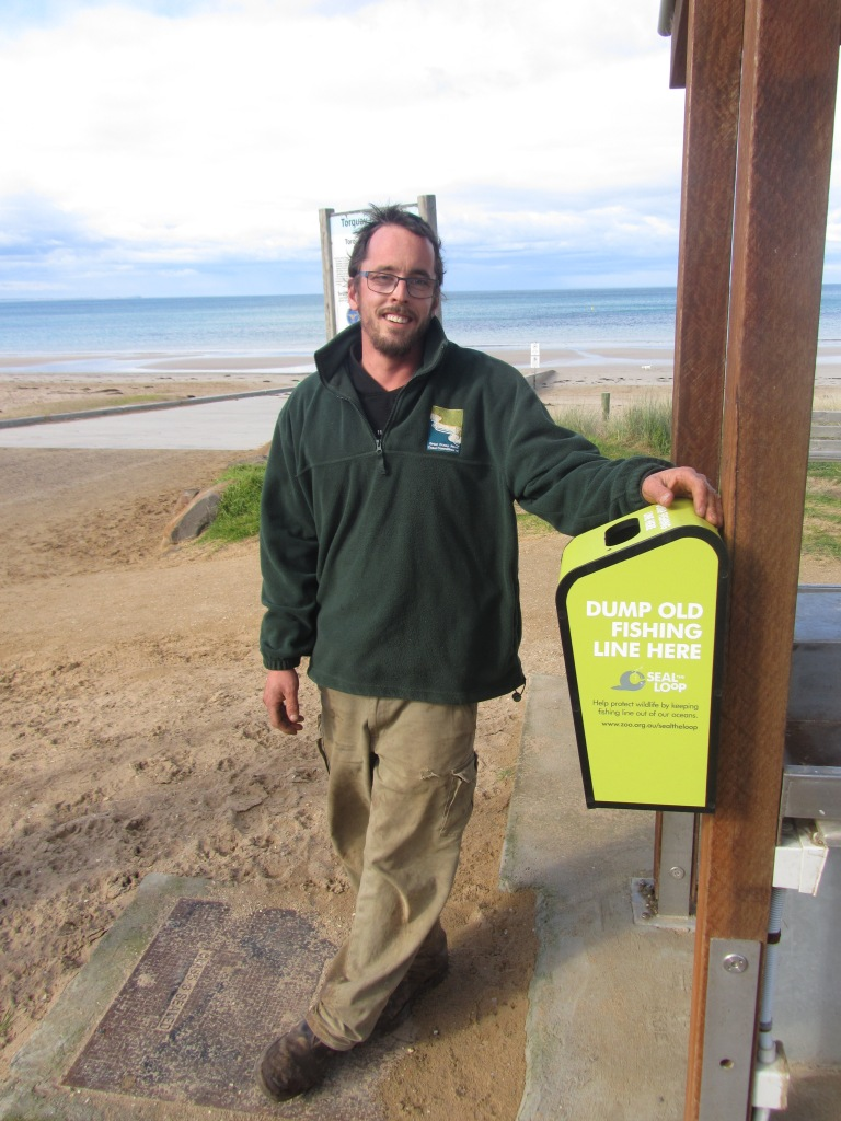 Great Ocean Road Coast Committee Reserves Outdoor Worker and keen angler Nick Farrant with a popular Seal the Loop bin at Fisherman's Beach.