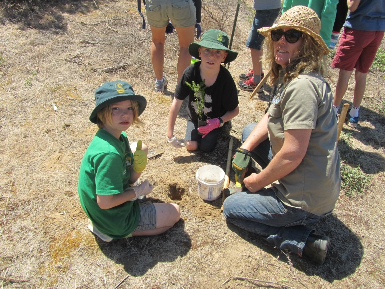 Conservation Supervisor Georgie Beale show students how to best protect indigenous plants by surrounding their roots with water crystals.