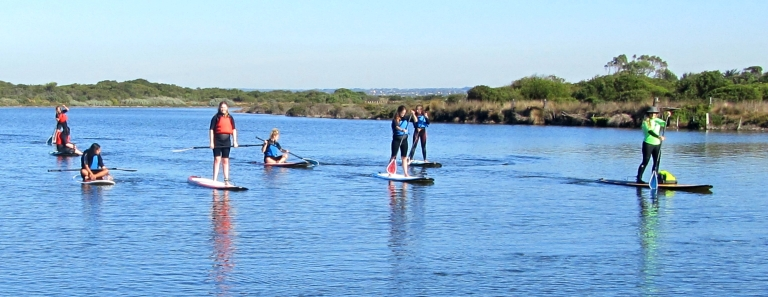 Students explore the river system on their paddle boards on a sunny autumn day.