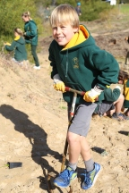Torquay College student digging a hole for the native plants.