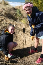 Two Torquay College students put stakes in the ground to help support the new Indigenous plants.