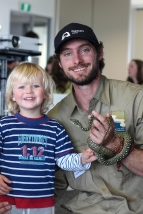 Pete Crowcroft and his son holding a python.