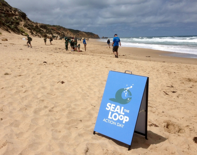 Students on the beach with Seal the Loop sign