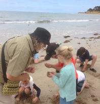 GORCC Education Activity Leader Hilary Bouma examines some of the treasures the Summer by the Sea participants found on the beach.
